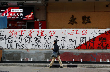 A man walks past graffiti sprayed by protesters on a wall in Hong Kong