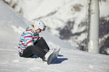 Snowboarder adjusting binding on her equipment
