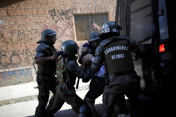 Members of the security forces detain a protester during a protest against Chile's government in Santiago