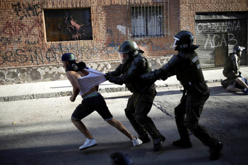 Security forces grab a protester as he runs away during a protest against Chile's government in Santiago