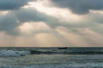 Acrylic Prints Nature Fishing boat in the splash waves of the ocean with sun rays, Varkala, India