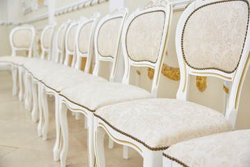 A row of white chairs of classic design in a bright room.