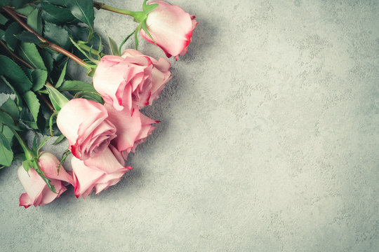 Flower arrangement - a bouquet of pink roses on a concrete surface, template for design or greeting card, place for text, copy space
