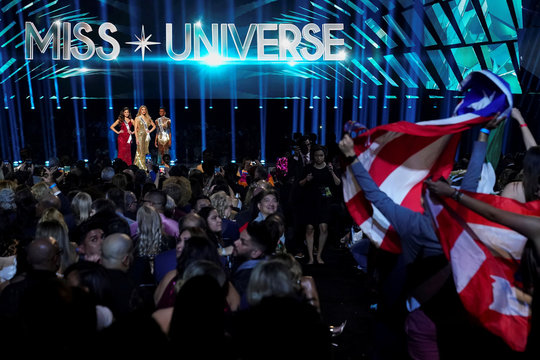 Fans wave the flags of Puerto Rico and Mexico as the final three contestants, from Mexico, Puerto Rico, and South Africa, compete in the Miss Universe pageant at Tyler Perry Studios in Atlanta