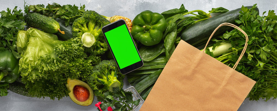 Grocery shopping concept. Smartphone with blank screen for your text message or design with paper bag, shopping cart and green vegetables Purchase healthy food