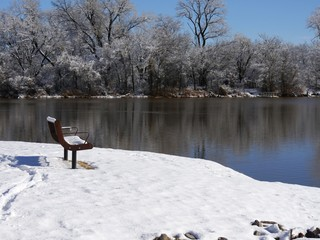 Medium wide scenic view by the pond on a winter morning, with a bench covered with snow