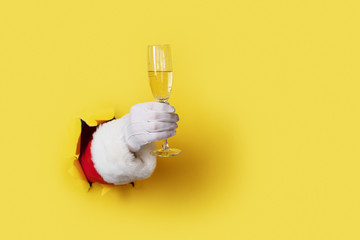 Santa Holding Champagne Flute isolated over light yellow. Hand and arm only