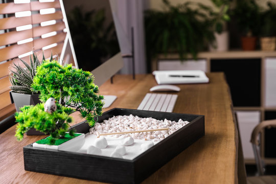 Modern workplace with beautiful miniature zen garden and computer in room