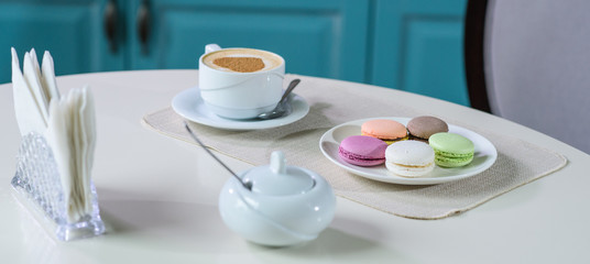 Aluminium Prints Macarons Delicious cappuccino and macaroons prepared on a table for a guest