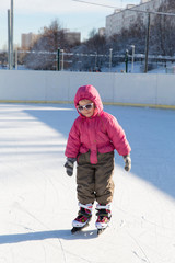 Happy little girl skating on the rink