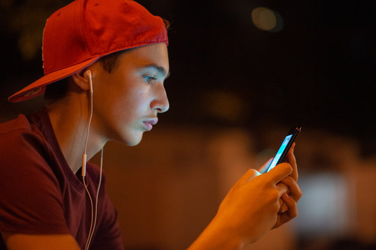 Close-up portrait of a young man with smartphone, on the city.   Teenage boy is using phone, outdoors.  Caucasian teenager in casual clothes with cell phone, urban scene. Soft focus effect.