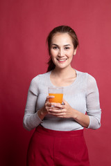 Young Asian woman drink orange juice.