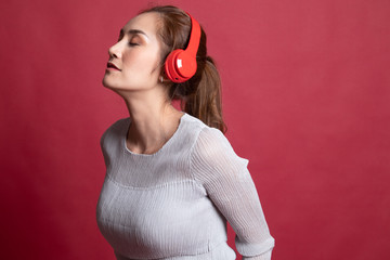 Pretty asian girl listening music with her headphones.