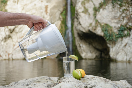 A hand pouring filtered water in the big glass with lemon on the nature background. Filter jug