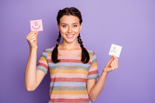 Photo of funny lady holding paper emoticons good and bad mood recommending positive emotions wear casual striped t-shirt isolated pastel purple color background