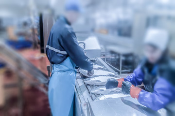 Blur, bokeh, background, abstract, image for background. Cutting the salmon on the production line in the fish processing plant