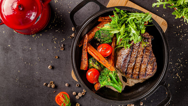 American food concept. Grilled beef steak with grilled vegetables, with carrots, cherry tomatoes, broccoli, in a cast iron pan. copy space