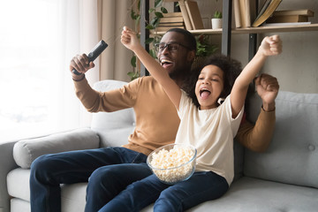 Happy black dad and daughter cheering watching football on TV Wall mural