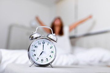 Closeup alarm clock having a good day with background happy woman stretching in bed after waking up, sunlight in morning. Waking up in the morning on time