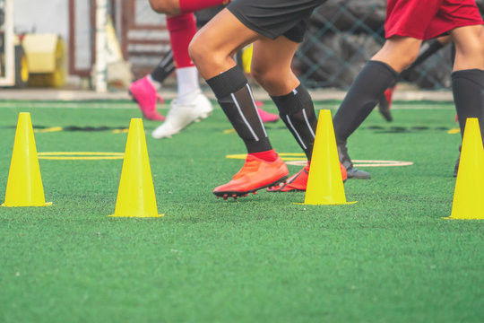 Children feet running and practicing on soccer field with cone and marker for football academy concept