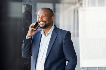 African mature businessman talking over phone