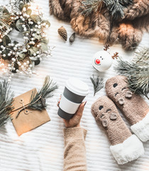 Female hand holding reusable eco  friendly coffee cup  on white knitted blanket with cedar branches, winter wreath, funny socks and craft paper envelope. Top view. Flat lay. Zero waste Christmas