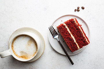 Top view of slice of red velvet cake with coffee on white background.