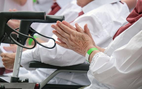 Nahaufnahme von Händen einer Seniorin in der Gruppe und Rollator im Vordergrund - selektiver Fokus