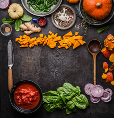 Vegetarian herbst and winter cooking background. Seasonal vegetables, herbs and spices with kitchen knife and wooden spoon. Frame. Top view. Copy space