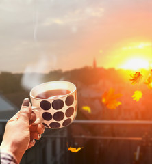 Woman hand holding cup with hot drink and steam at autumn city background with flying leaves and sunset light