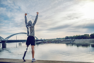 Highly motivated caucasian handicapped sportsman in sportswear and with artificial leg standing on quay and holding arms up. Only way to win is to be yourself. Fotomurales