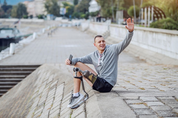 Fotomurales - Attractive Caucasian handicapped sportsman in sportswear and with artificial leg listening music over smart phone and waving to a friend while sitting on quay.