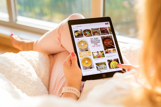 Riga, Latvia - July 21, 2018: Woman using Pinterest app on iPad.