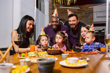 Portrait of happy multiethnic family celebrating a birthday at home. Big family eating cake and drinking wine while greeting and having fun children. Celebration, family, party, home concept.