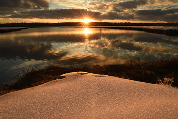 Fotobehang - Winter landscape water reservoir at sunset. Beautiful sunset sky, the sun setting over the horizon and sparkling clear snow.