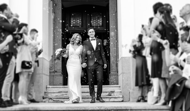 Newlyweds exiting the church after the wedding ceremony, family and friends celebrating their love with the shower of soap bubbles, custom undermining traditional rice bath. Black and white.