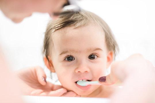 Happy 1 year old Baby in bathtubbrushing teeth in bathroom with mother.