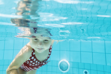 Happy family in swimming pool. Smiling child swim, dive in pool with fun - jump deep down...