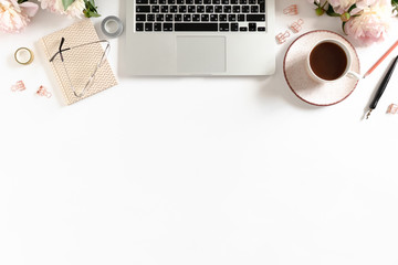 White table with laptop, mug of coffee, pink peonies and stationery
