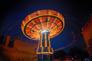 spinning carousel at amusement park.night time