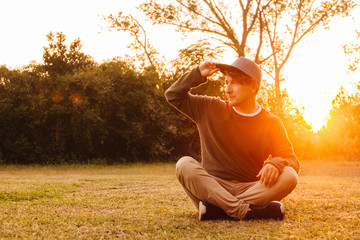 Young man sitting down on the green grass, enjoying a sunset relaxation in a park. Concept of freedom relaxation. Place for text or advertising