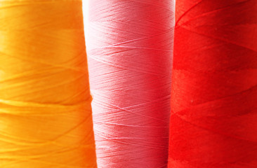 Close-up colorful spools of thread background.