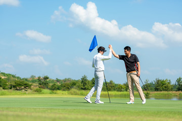 Group Professional Golfer asian man shake hand for friendship after finish put ball on green. Hobby relax in holiday and vacation with friends. Lifestyle and Sport Concept