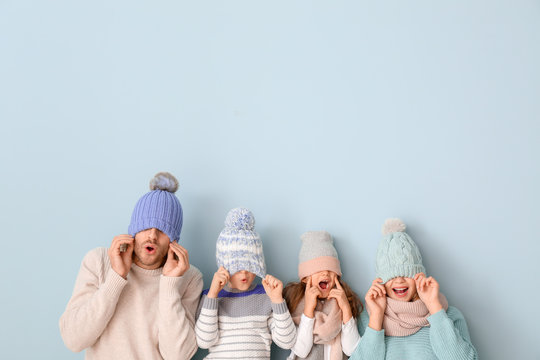 Happy family in winter clothes on color background