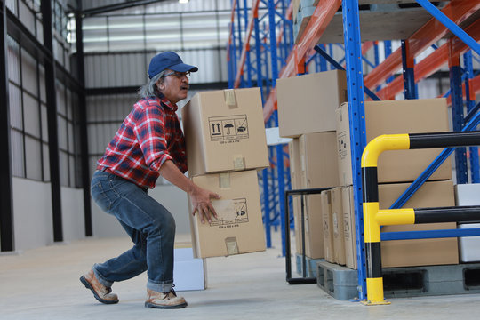 Asian worker man hurt his back .lift heavy box in factory