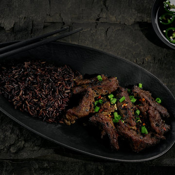 Chinese black pepper beef stir fry with black rice in a black clay plate on an old rustic table. Directly above top view shot.