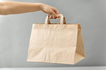 recycling, shopping and ecology concept - hand holding disposable brown takeaway food in paper bag with lunch on table