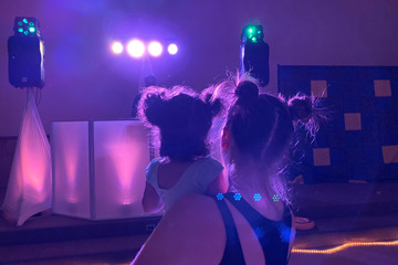 "Iliana Hazzard holds her 20-month-old daughter Daphne while facing the DJ booth at a ""Baby Rave"" in Oakland"