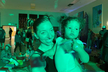 "Iliana Hazzard holds her 20-month-old daughter Daphne at a ""Baby Rave"" in Oakland"