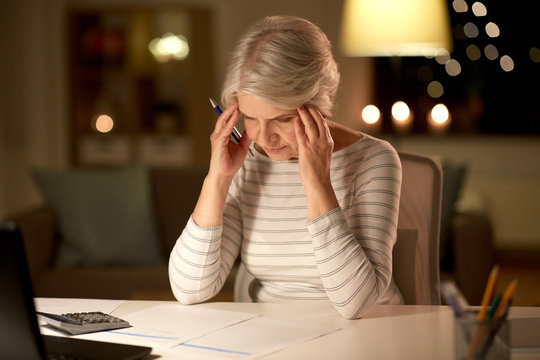 old age and stress concept - stressed senior woman filling tax form at home in evening